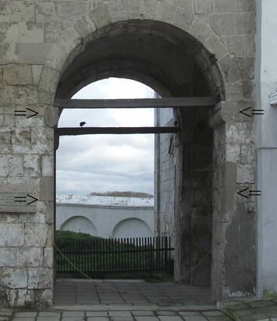Arch under the northern passage. The traces of turnings at the places of the gate hinges are marked by arrows.